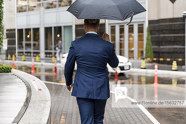 Rückansicht eines jungen Geschäftsmannes mit Regenschirm während eines Regentages in Bangkok