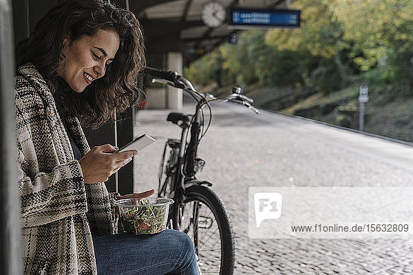 Smiling woman with bicycle having lunch and using smartphone on station platform  Berlin  Germany