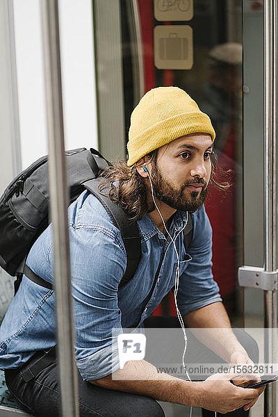 Mann mit Rucksack beim Musikhören mit Smartphone und Kopfhörern in Pendlerlinie  Berlin  Deutschland