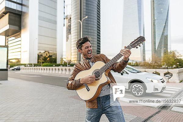 Aufgeregter Mann spielt Gitarre in der Stadt  Madrid  Spanien