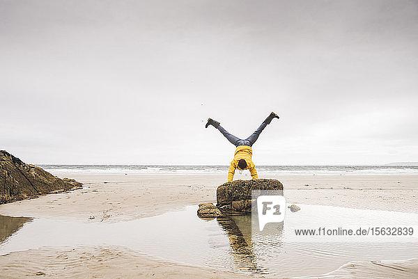 Junger Mann trägt gelbe Regenjacke am Strand und macht einen Handstand auf einem Felsen  Bretagne  Frankreich