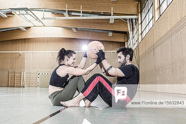 Mann und Frau üben mit Medizinball in Sporthalle