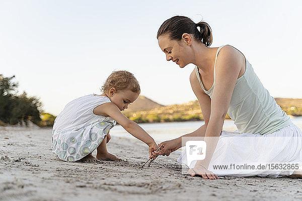 Mutter und Tochter zeichnen mit kleinen Stöckchen im Sand am Strand