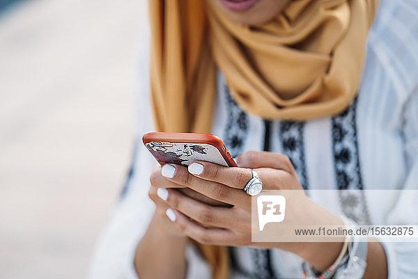 Junge muslimische Frau trägt gelben Hijab und benutzt Smartphone
