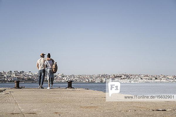 Junges Paar steht am Pier am Wasser  Lissabon  Portugal