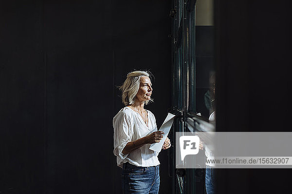 Casual mature businesswoman looking out of window in loft office