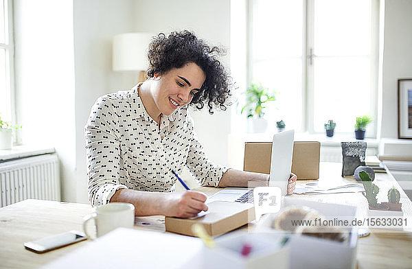 Lächelnde junge Frau bereitet am Schreibtisch ein Paket vor