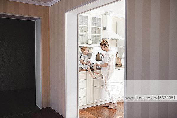 Mutter macht Tee mit ihrem kleinen Jungen in der Küche