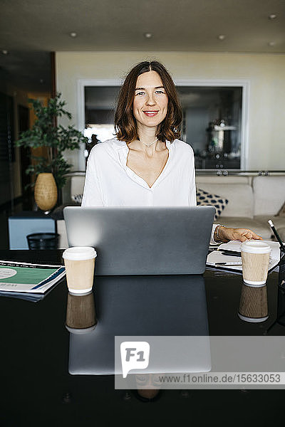 Portrait of smiling woman working on table at home with laptop