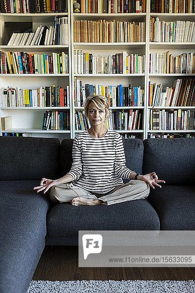 Reife Frau  die zu Hause auf der Couch Yoga praktiziert