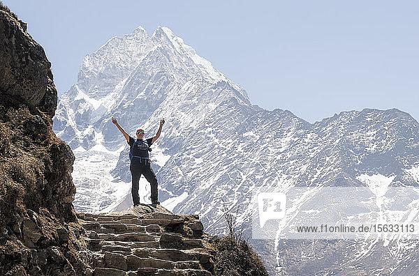 Glückliche Frau hebt die Arme vor dem Berg Thamersku  Himalaja  Solo Khumbu  Nepal