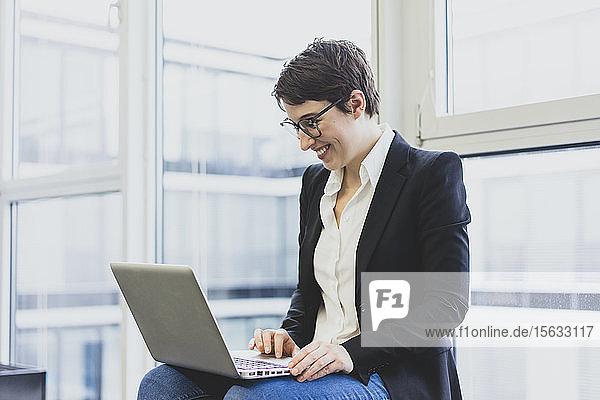 Lächelnde junge Geschäftsfrau mit Laptop am Fenster