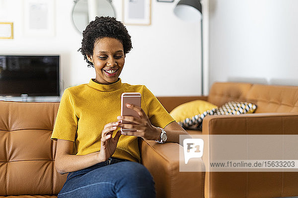 Smiling young woman sitting on couch at home using smartphone