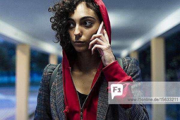 Porträt einer jungen Frau am Telefon am Abend