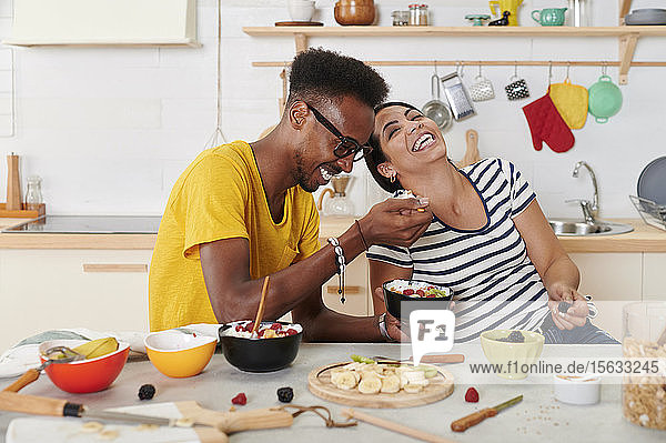 Multiethnic couple laughing  breakfasting together in the kitchen