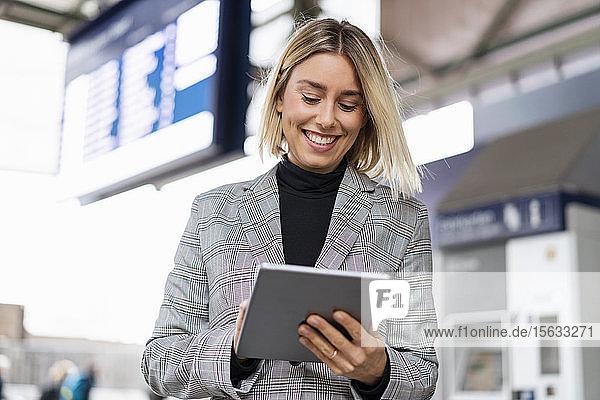 Lächelnde junge Geschäftsfrau mit Tablette am Bahnhof