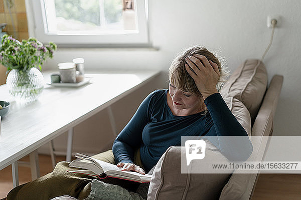 Frau sitzt auf Couch und liest einen Roman