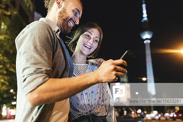 happy couple using smartphones in the city at night  Fernsehturm in the background  Berlin  Germany