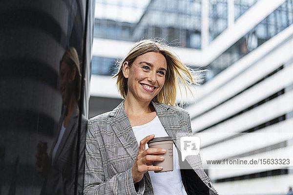 Fröhliche junge Geschäftsfrau mit Kaffee zum Mitnehmen in der Stadt