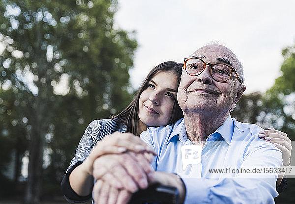 Porträt eines älteren Mannes und seiner Enkelin in einem Park