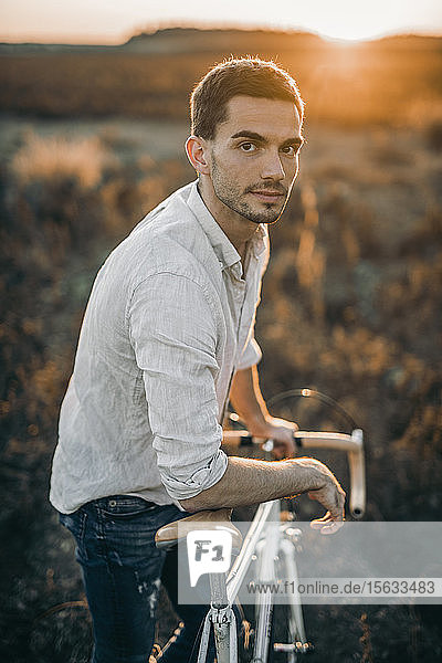 Portrait of a young man with his racing bicycle in sunshine