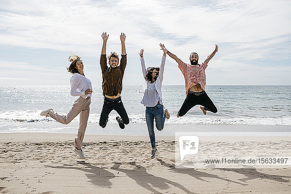 Exuberant friends jumping on the beach