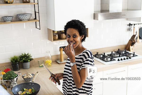 Porträt einer lächelnden jungen Frau  die zu Hause in der Küche kocht und Gemüse probiert