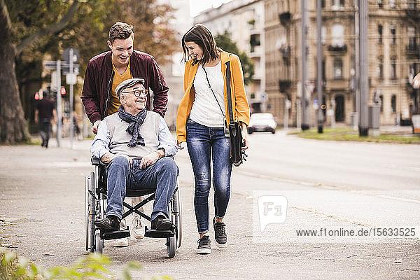 Happy senior man in wheelchair spending time with his grandchildren