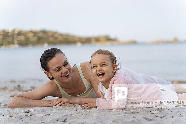 Glückliche Mutter mit Tochter am Strand liegend