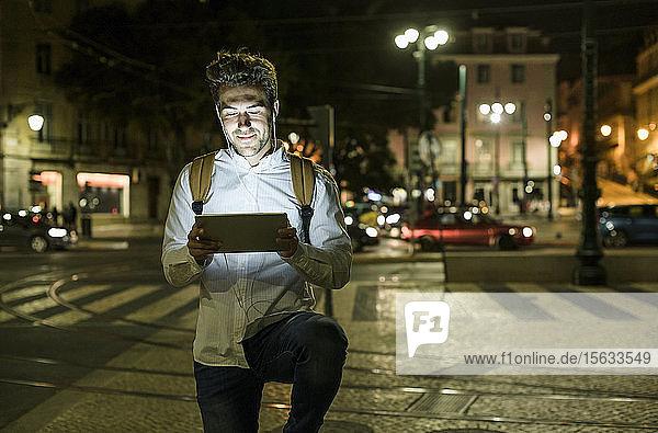 Porträt eines jungen Mannes mit digitalem Tablet und Kopfhörern in der Stadt bei Nacht  Lissabon  Portugal