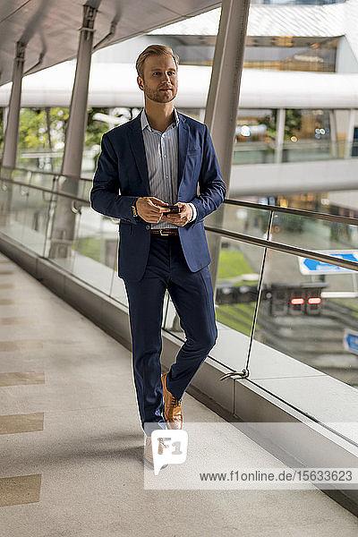Junger Geschäftsmann auf Fußgängerbrücke