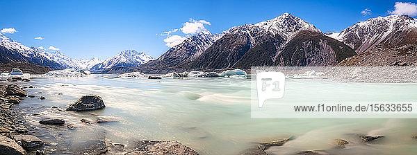 Neuseeland  Südinsel  felsiges Ufer des Tasman Lake mit Eisbergen  Gletscher und Bergkulisse