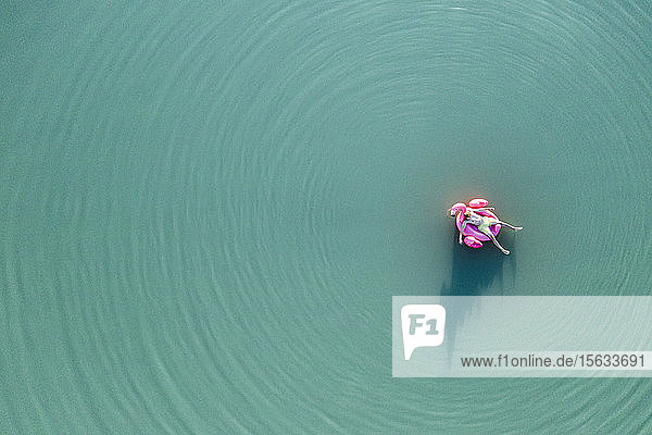 Young man with flamingo pool float on the lake
