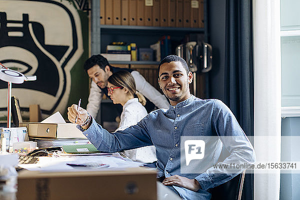 Young man working in architect's office  looking at camera
