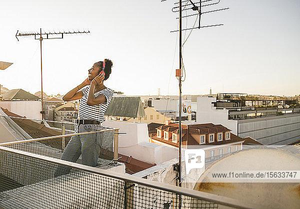 Glückliche junge Frau steht bei Sonnenuntergang auf dem Dach und hört Musik mit Kopfhörern
