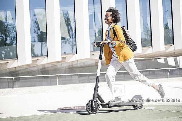 Glückliche junge Frau mit Kopfhörern auf einem E-Scooter in der Stadt