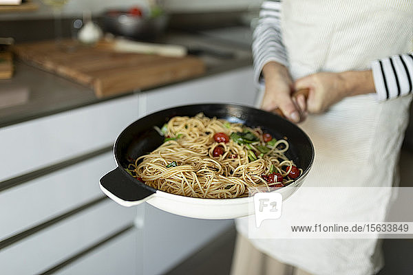 Close-up of woman holding a pan with pasta dish in kitchen at home