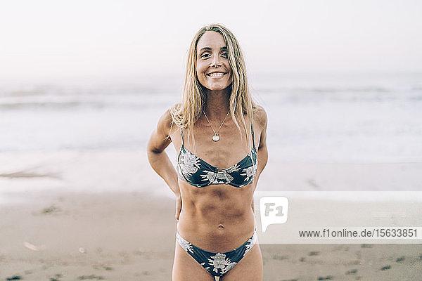 Junge blonde Frau im Bikini am Strand