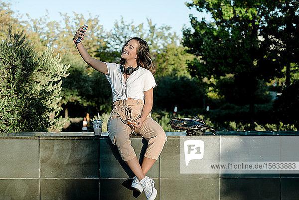 Junge Frau mit Hamburger  die einen Selfie mit dem Smartphone macht