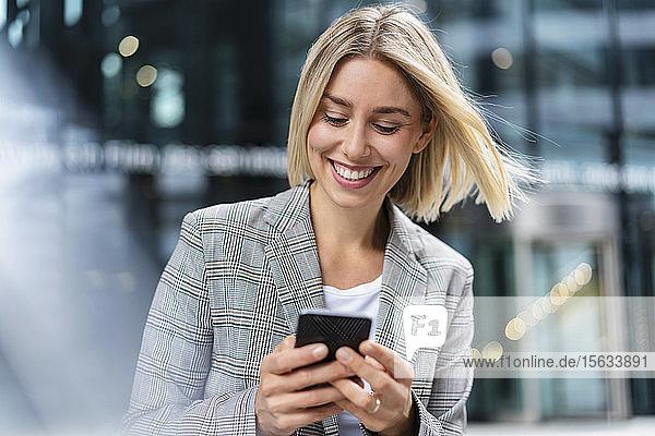 Glückliche junge Geschäftsfrau benutzt Mobiltelefon in der Stadt