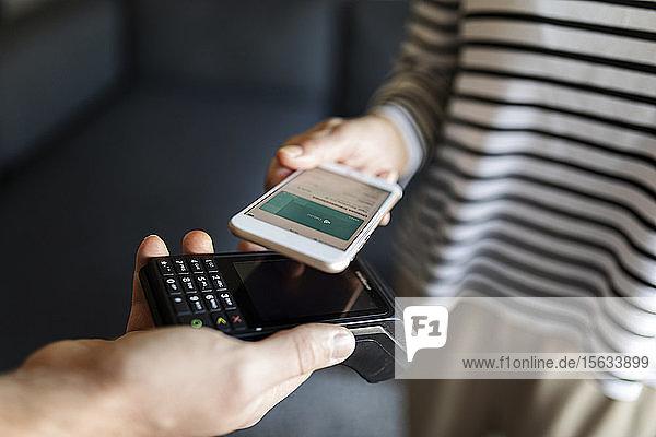 Nahaufnahme einer Frau  die zu Hause mit dem Handy bezahlt