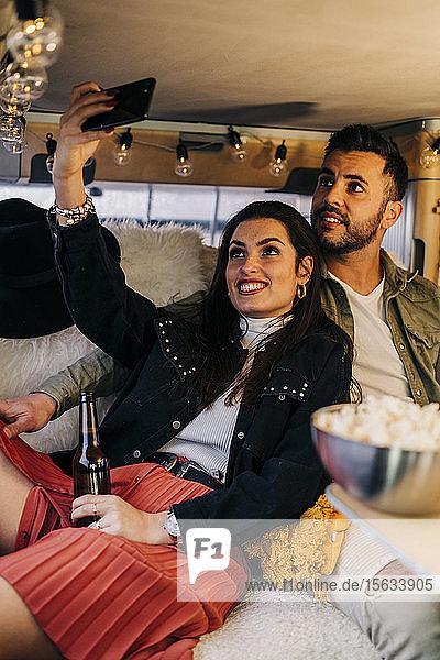 Glückliches junges Paar mit einem Selfie im Wohnmobil