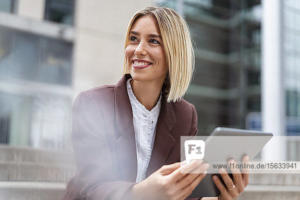 Lächelnde junge Geschäftsfrau mit Tablette in der Stadt