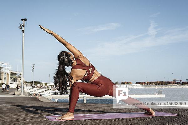 Rückansicht einer asiatischen Frau  die im Hafen Yoga praktiziert Rückansicht einer asiatischen Frau, die im Hafen Yoga praktiziert