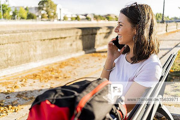 Junge Rucksacktouristin mit rotem Rucksack und Smartphone  auf einem benach in Verona  Italien