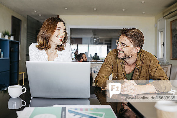 Happy man and woman working together with laptop on table at home