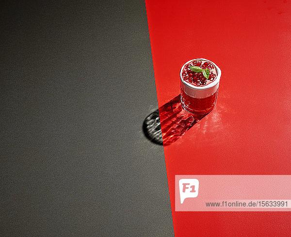 Hochwinkelansicht eines Granatapfelgetränks auf farbigem Hintergrund
