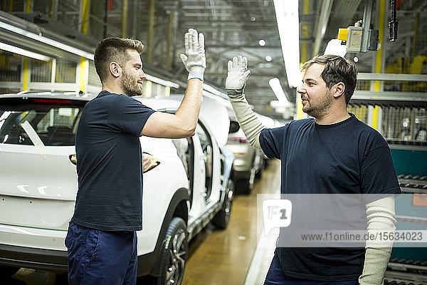 Zwei Kollegen geben sich in moderner Autofabrik die Klinke in die Hand