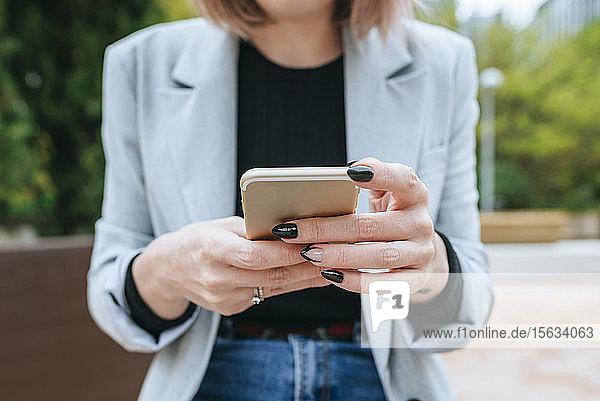 Nahaufnahme einer Frau  die im Freien ein Mobiltelefon benutzt