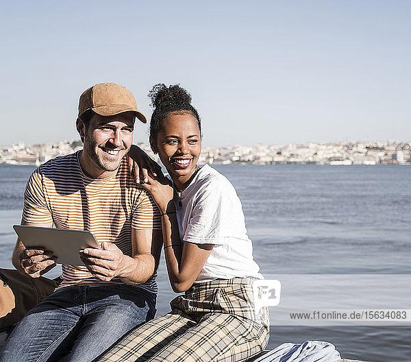 Glückliches junges Paar sitzt mit einer Tablette am Wasser  Lissabon  Portugal